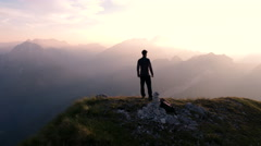 Aerial - Flying around young man standing victoriously on top of the mountain Stock Footage