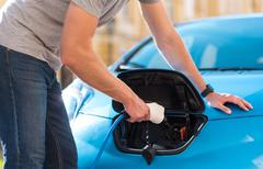 Man plugging cable in hybrid car Stock Photos