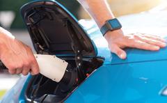 Man charging his hybrid car - stock photo