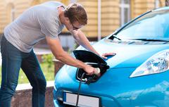 Man charging battery of eco car - stock photo