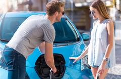 Man helping woman to charge car Stock Photos
