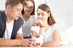 Teenagers on the biology lesson. - stock photo