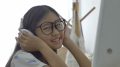 4K : Attractive Asian girl listening music on computer with headphone Stock Footage