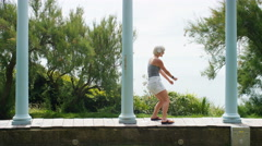 Attractive woman in shorts dances between pillars whilst listening to music Stock Footage