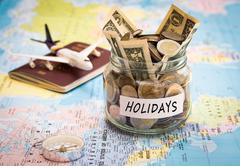 Holidays budget concept with compass, passport and aircraft toy Stock Photos