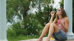 Young woman sitting down blowing bubbles, in slow motion - stock footage