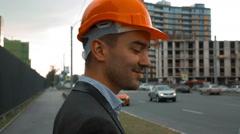 Builder in a orange helmet is making call Stock Footage