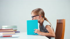 Happy schoolgirl 7-8 years old holding book on her head and smiling at camera Stock Footage