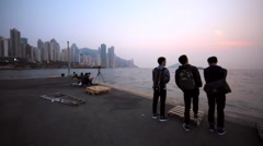 View of group of people enjoying beautiful sea sunset. Evening in Hong Kong. Stock Footage