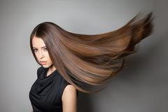 Beautiful model with smooth flying hair - stock photo