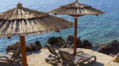 Rocky beach and thatched umbrellas Stock Footage