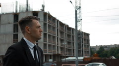 Businessman in suit walking near newly constructed building Stock Footage