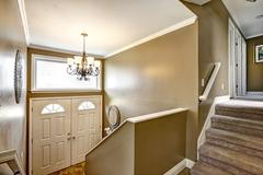 Entryway in small American home with mocha walls and white trim, staircase wi - stock photo