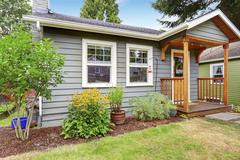 Small American house with gray exterior paint and small covered porch. Green  - stock photo