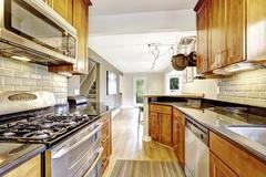 Practical kitchen room interior. Cabinets, steel appliances, granite tops and - stock photo