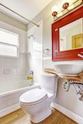 Refreshing bathroom interior. Red cabinet with mirror and white vessel sink.  - stock photo