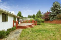 One story house with wooden walkout deck with railings and stairs.  Northwest - stock photo
