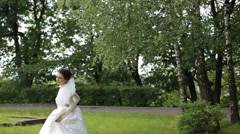 Funny bride walking and jumping in the park - stock footage