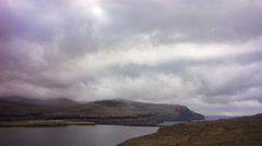 Moving clouds above the mountains and a lake, Faroe Islands, 4K time lapse Stock Footage