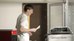 Young man printing in the office Stock Footage