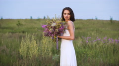 Young girl walks on a sunset on summer field with a bouquet of flowers Stock Footage