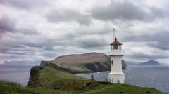 Remote lighthouse on an island with steep cliffs, Faroe Islands, 4K time lapse Stock Footage