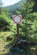 Vertical photo of blank prohibition sign and mountain wood landscape. Stock Photos