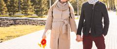 Young couple in love walking in the autumn park holding hands Stock Photos