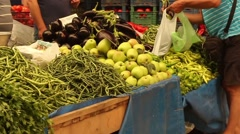 Customers buying goods from Turkish veg market stall filmed at 60fps Stock Footage