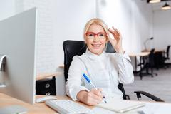 Portrait of a smiling mature businesswoman using laptop in office - stock photo