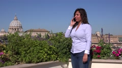 Beautiful woman talking on mobile phone in the city rooftop terrace Rome Vatican - stock footage