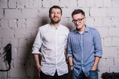 Two young men startupers over grey brick wall loft interior design Stock Photos