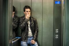 Scared young man desperate in stuck elevator Stock Photos