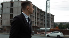 Businessman in suit walking near newly constructed building - stock footage