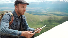 Man's hands touching screen of digital tablet on the background of mountains Stock Footage
