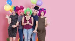Group of young women disguised for a party, with candies, ballons and wigs. Stock Photos