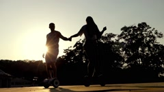 Young Couple Dancing and Riding on Segways. Slow Motion at Sunset. Happy Stock Footage