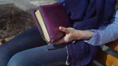 Woman sitting on a bench in the park and reading books of the Bible Stock Footage