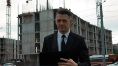 Businessman using digital pad near new construction Stock Footage