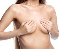 Sexy naked woman covering her breasts with hands. Close-up Stock Photos