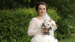 Bride walking and smilling with her bouquet in the park - stock footage