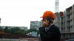 Builder in helmet talking on a smart phone Stock Footage