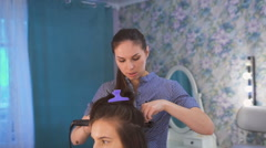 A professional hair stylist preparing beautiful bride before the wedding in a Stock Footage