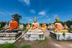 Many Budddha statues against blue sky Stock Photos