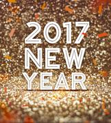 happy new year 2017 year number with confetti at sparkling golden glitter bac - stock illustration