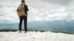 Hiker looking at view in high altitude mountain above the clouds - stock footage
