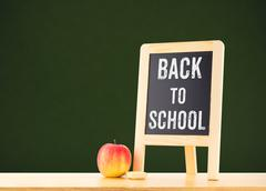 Back to school word on blackboard on wood table with apple at green backgroun - stock photo