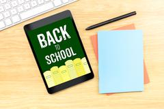 Back to school word on tablet screen with book pencil and keyboard on wood ta Stock Photos