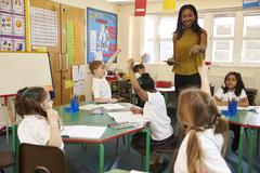 Teacher With Digital Tablet In Elementary School Classroom Stock Photos
