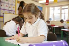 Pupil Working At Desks In Elementary School Classroom Stock Photos